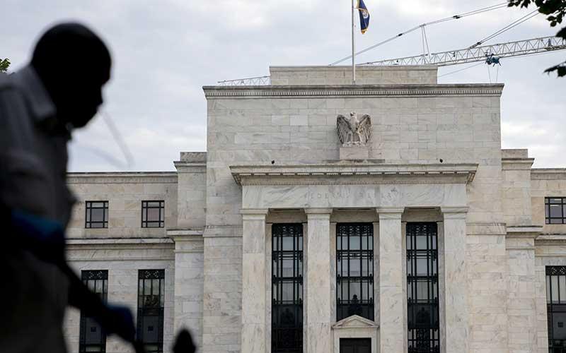 Warga melintas di depan gedung bank central Amerika Serikat atau The Federal Reserve di Washington, Amerika Serikat, Rabu (31/7/2019). Bloomberg - Andrew Harrer