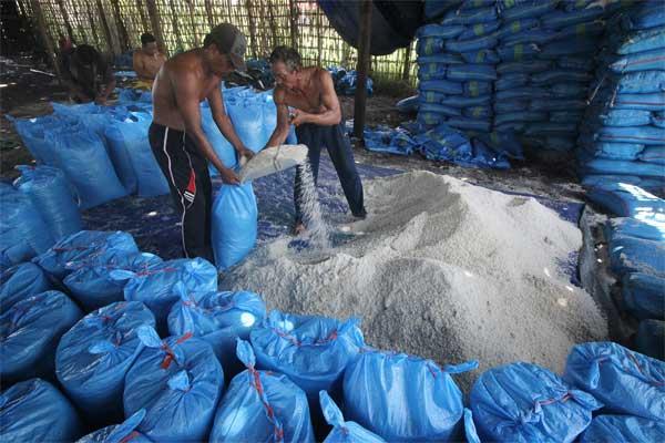 Pekerja mengemas garam ke dalam karung di salah satu gudang penyimpanan garam di Surabaya, Jawa Timur, Senin (15/5). - Antara/Moch Asim