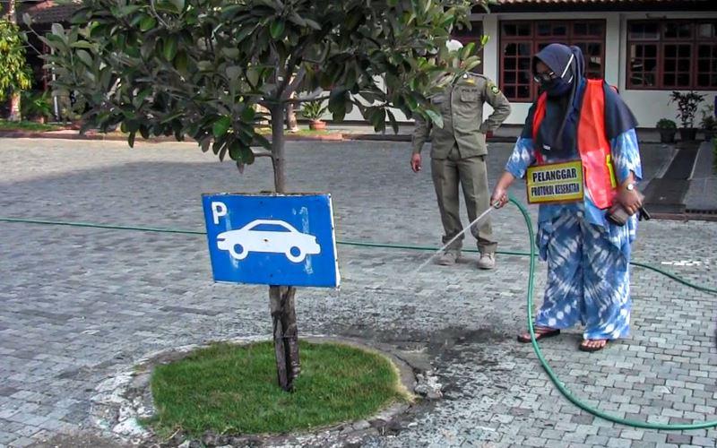 Salah satu pelanggar protokol kesehatan saat menjalani sanksi kerja sosial menyirami tanaman di halaman Pemkab Kulonprogo, Kamis (17/9/2020). - Harian Jogja/Jalu Rahman Dewantara