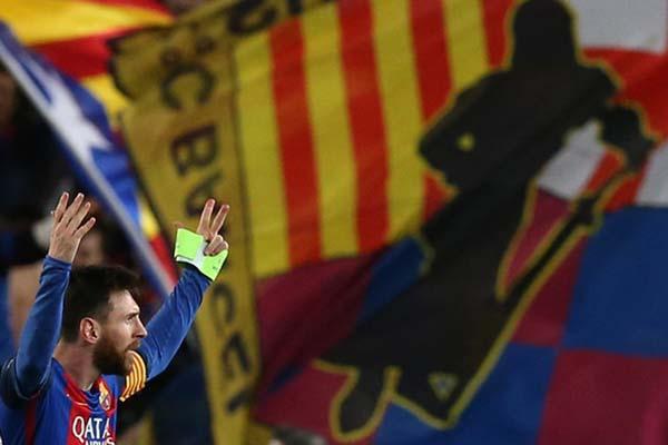 Lionel Messi berlatar belakang bendera FC Barcelona. - Reuters