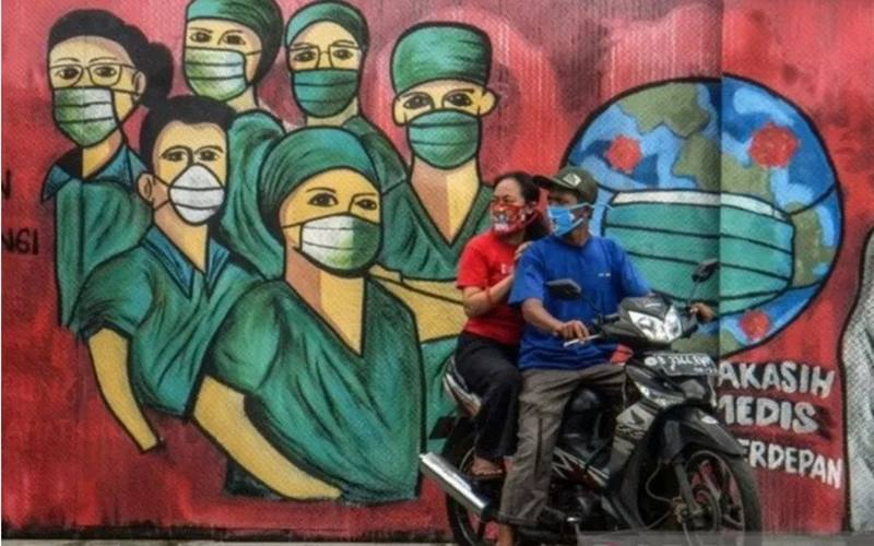 Pengendara motor melintas di depan mural tentang pandemi Covid-19 di Jalan Raya Jakarta-Bogor, Depok, Jawa Barat, Jumar (3/4/2020). - Antara