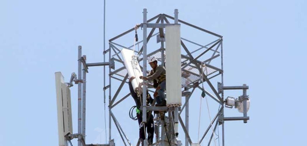 Teknisi memasang perangkat Base Transceiver Station (BTS) di salah satu tower di Makassar, Sulawesi Selatan, Rabu (18/3/2020). - Bisnis/Paulus Tandi Bone\\r\\n