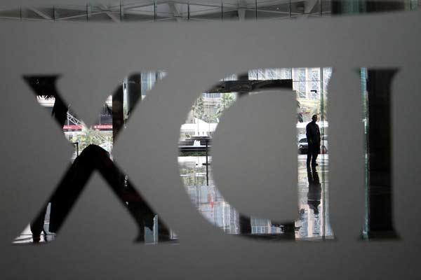 Siluet karyawan melintasi logo IDX Indonesia Stock Exchange di gedung Bursa Efek Indonesia Jakarta.  - Bisnis.com/Dwi Prasetyo