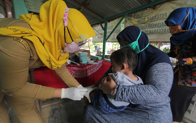 Kader Pos Pelayanan Terpadu (Posyandu) memberikan vaksin imunisasi kepada balita di Posyandu Kunir, Desa Sukaurip, Balongan, Indramayu, Jawa Barat, Senin (10/8/2020). Pemerintah mulai mengaktifkan kembali posyandu desa yang sempat terhenti sejak pandemi COVID-19 dengan memperketat protokol kesehatan dan menyesuaikan kondisi Adaptasi Kebiasaan Baru. ANTARA FOTO - Dedhez Anggara