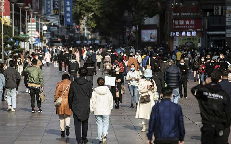 Warga menggunakan masker saat berjalan melewati toko-toko di Nanjing Road di Shanghai, China, Sabtu (14/3/2020). Bloomberg - Qilai Shen