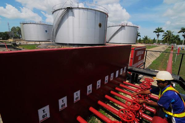 Petugas memutar kontrol water sprinkler guna mendinginkan tangki depo BBM milik PT Pertamina di Merauke, Papua, Selasa (29/10). Depot BBM yang berkapasitas 9.500 KL tersebut merupakan salah satu depot di perbatasan Indonesia - papua Nugini yang menyalurkan premium, kerosin, solar dan avtur. - antara
