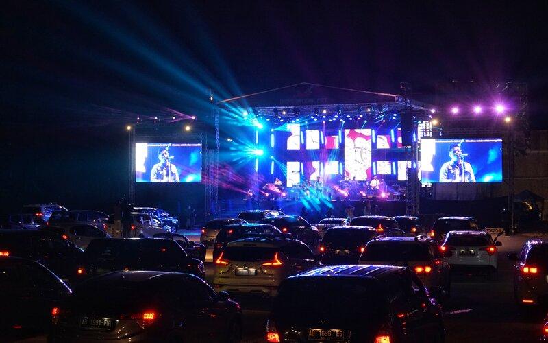 Penonton menyaksikan penampilan band Jikustik dari dalam mobil saat konser musik drive-in di Sleman City Hall, D.I Yogyakarta, Minggu (20/9/2020). Konser musik drive-in pertama di Yogyakarta itu digelar dengan menerapkan protokol kesehatan untuk mencegah penyebaran Covid-19. - Antara/Andreas Fitri Atmoko