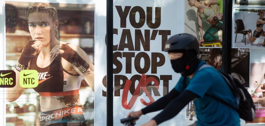 Seorang pesepeda melewati gerai Nike di Bonifacio Global City, Metro Manila, Filipina, Senin (27/7/2020). - Bloomberg/Geric Cruz