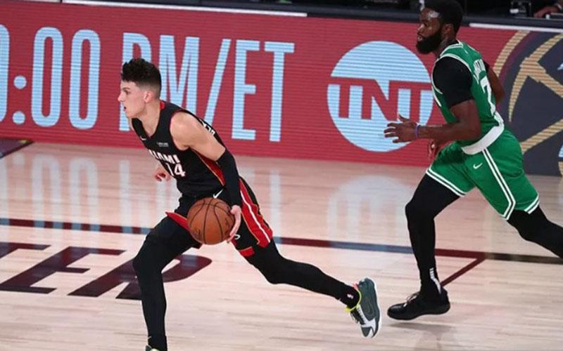 Guard Miami Heat Tyler Herro (14) membawa bola dikejar guard Boston Celtics Jaylen Brown saat bertanding di gim keempat final Wilayah Timur./Antara - Reuters