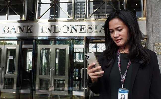 Karyawan melintas di dekat logo Bank Indonesia.