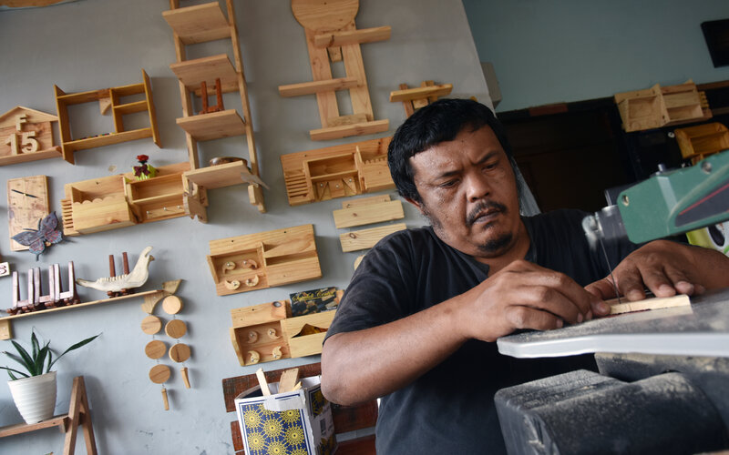 Seorang perajin membuat suvenir dari bahan baku limbah kayu palet di bengkel Urban Green Interior, di Kota Pekanbaru, Riau, Selasa (1/9/2020). Perajin di Bengkel Urban Green Interior lahir dari pelaku industri kreatif yang kehilangan pekerjaan akibat pandemi Covid-19, dengan mengolah limbah kayu untuk suvenir dan dijual dengan harga berkisar Rp25.000 hingga Rp500.000 tergantung model dan tingkat kesulitan produknya. - Antara/FB Anggoro