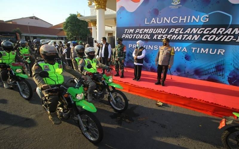 Gubernur Jawa Timur Khofifah Indar Parawansa (kedua kanan), Pangdam V/Brawijaya Mayjen TNI Widodo Iryansyah (ketiga kanan) dan Kapolda Jawa Timur Irjen Pol M Fadil Imran (kanan) melepaskan tim pemburu pelanggaran protokol kesehatan Covi-19 saat diluncurkan di Gedung Negara Grahadi, Surabaya, Jawa Timur, Rabu (16/9/2020). - Antara/Moch Asim