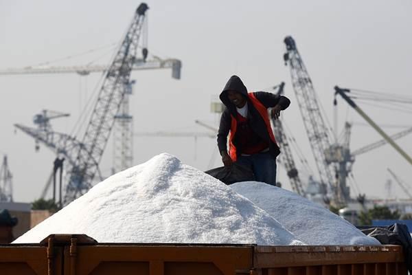Ilustrasi. Petani garam sedang merapikan tumpukan garam miliknya. - Antara/Zabur Karuru