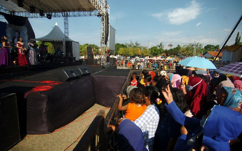 Sejumlah warga tidak mengenakan masker menyaksikan musik dangdut di Lapangan Tegal Selatan, Tegal, Jawa Tengah, Rabu (23/9/2020). Konser musik dangdut yang diadakan Wakil Ketua DPRD Kota Tegal Wasmad untuk perayaan pernikahan di tengah pandemi Covid-19 tersebut dihadiri banyak warga yang tidak menerapkan protokol kesehatan dengan tidak memakai masker dan tidak jaga jarak. - Antara - Oky Lukmansyah