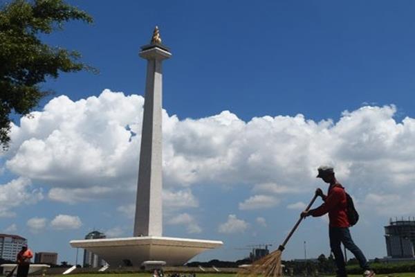 Pekerja harian Lepas (PHL) membersihkan sampah di sepanjang jalan di kawasan Monas, Jakarta, Selasa (17/3). - Antara