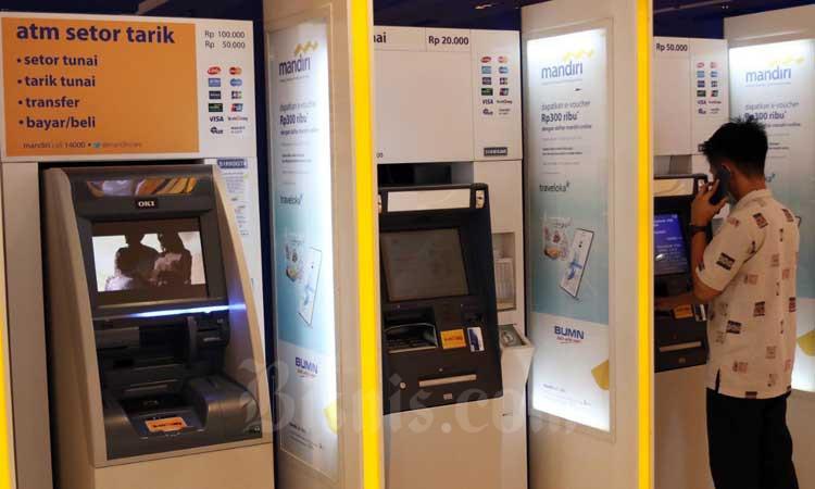 Nasabah mengambil uang di Anjungan Tunai Mandiri (ATM) Bank Mandiri di nJakarta, Selasa (10/3/2020). Bisnis - Eusebio Chrysnamurti