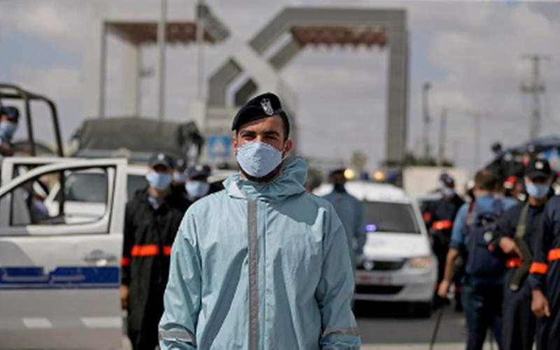 Anggota pasukan keamanan Hamas Palestina mengenakan masker pelindung saat berjaga di perlintasan perbatasan Rafah dengan Mesir, yang dibuka kembali untuk pertama kalinya sejak ditutup pada Maret karena kekhawatiran Covid-19, di Jalur Gaza selatan (11/8/2020)./Antara - Reuters/Ibraheem Abu Mustafa