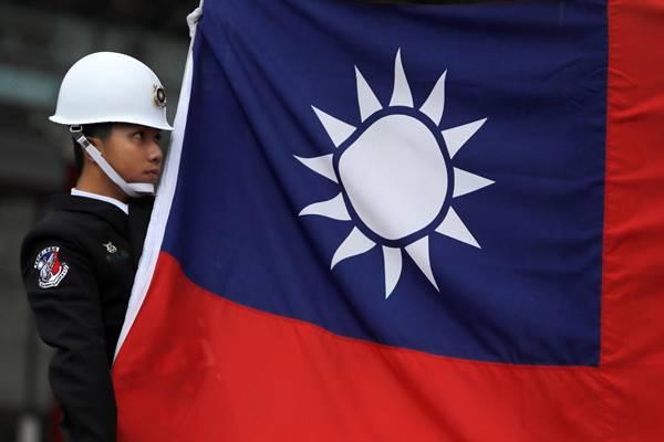 Seorang militer memegang bendera nasional Taiwan saat menghadiri upacara pengibaran bendera di Chiang Kai-shek Memorial Hall, di Taipei, Taiwan, 16 Maret 2018. - Reuters