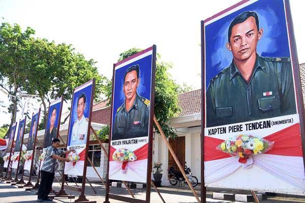 Pegawai memasang gambar pahlawan revolusi di halaman Gedung Negara Grahadi, Surabaya, Jumat (29/9). Pemasangan gambar tersebut dalam rangka menyambut Hari Kesaktian Pancasila 1 Oktober, sekaligus untuk mengenang korban peristiwa G30S/PKI, khususnya Tujuh Pahlawan Revolusi. ANTARA FOTO - M Risyal Hidayat