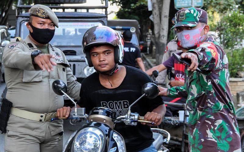 rnSatgas gabungan menjaring warga tidak memakai masker saat digelar Operasi Yustisi Protokol COVID-19 di Pusat Kota Lhokseumawe, Aceh, Rabu (16/9/2020). Operasi itu menerapkan sanksi sosial cabut rumput dan membersihkan sampah bagi warga tidak bermasker untuk meningkatkan disiplin dan kepatuhan terhadap protokol kesehatan sebagai upaya pencegahan dan pengendalian penyebaran COVID-19 yang terus meningkat di Aceh. ANTARA FOTO - Rahmad