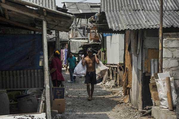 Warga beraktivitas di rumah semi permanen yang berada di kawasan Muara Angke, Penjaringan, Jakarta, Minggu (11/6). - Antara/Aprillio Akbar