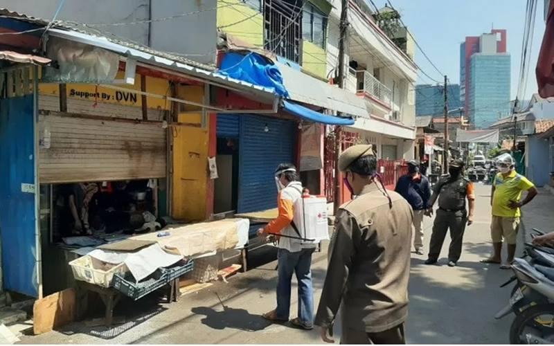 Petugas dari Kelurahan Karet Kuningan, Jakarta Selatan, melakukan penyemprotan disinfektan di lingkungan Pasar Ciplak yang ditutup karena pedagang terpapar Covid-19, Senin (28/9/2020. - Antara