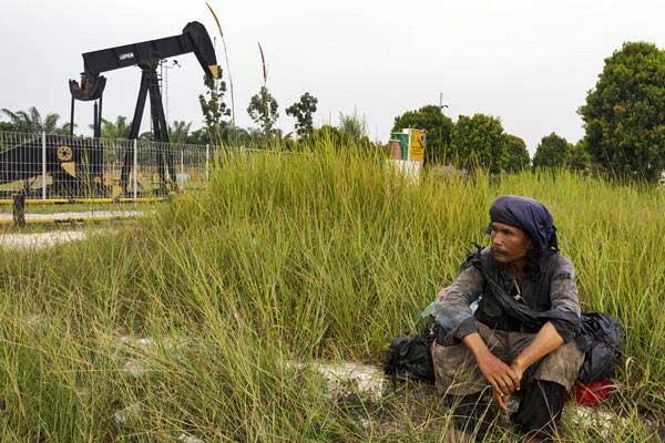 Warga beristirahat di dekat monumen pompa angguk minyak tertua di daerah Minas yang masuk dalam Blok Rokan di Riau, Rabu (1/8/2018). - ANTARA/FB Anggoro