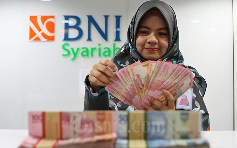 Karyawan menghitung uang rupiah di Kantor Bank BNI Syariah di Jakarta, Senin (24/2 - 2020)