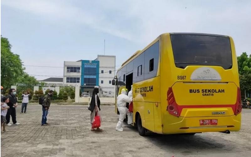 Petugas Unit Pengelola Angkutan Sekolah (UPAS) Dinas Perhubungan DKI Jakarta mengevakuasi pasien Covid-19 menggunakan bus jemputan sekolah dari sejumlah Puskesmas di Jakarta, Senin (28/9/2020). - Antara