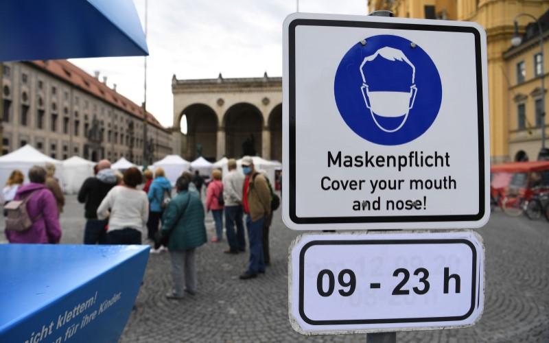 Papan aturan penggunaan masker di ruang publik di Jerman. - Bloomberg