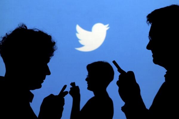 Ilustrasi orang sedang memegang ponselnya dengan latar belakang logo Twitter. - Reuters/Kacper Pempel