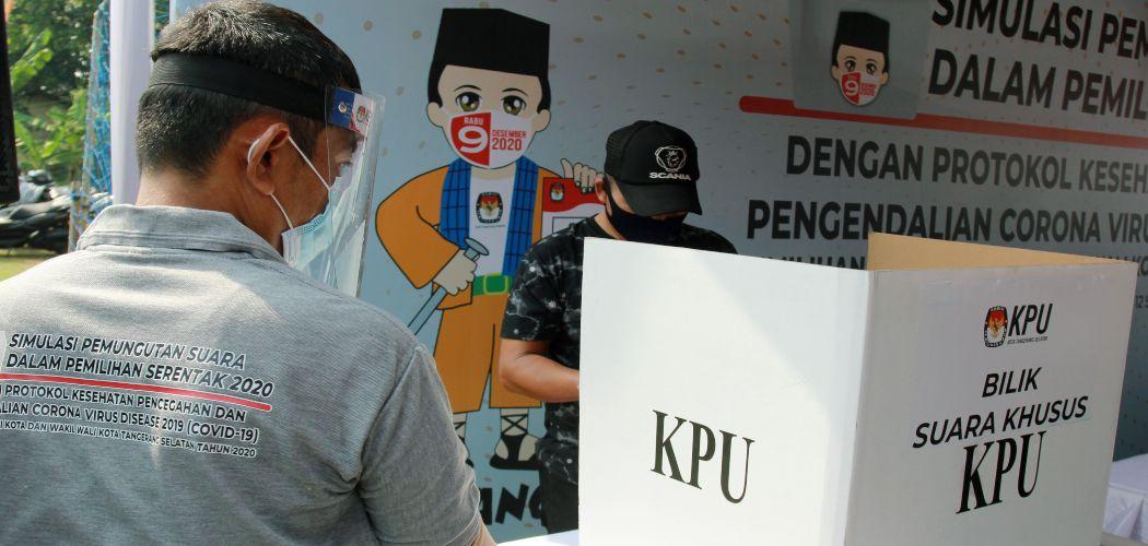 Petugas Kelompok Penyelenggara Pemungutan Suara (KPPS) dengan menggunakan alat pelindung diri (APD) mengawasi pemilih di bilik suara khusus saat simulasi pemungutan suara dengan protokol kesehatan pencegahan dan pengendalian COVID-19 di TPS 18 Cilenggang, Serpong, Tangerang Selatan, Banten, Sabtu (12/9/2020). ANTARA FOTO/Muhammad Iqbal - pra