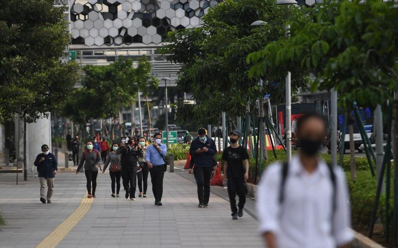 Sejumlah pekerja berjalan usai bekerja dengan latar belakang gedung perkantoran di Jl. Jenderal Sudirman, Jakarta, Kamis (16/4/2020). - ANTARA FOTO/Akbar Nugroho Gumay