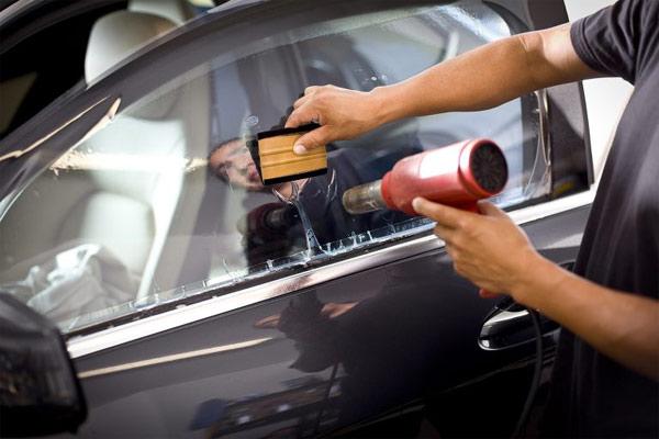 Teknisi menempelkan film pada kaca mobil.  - Solar Gard