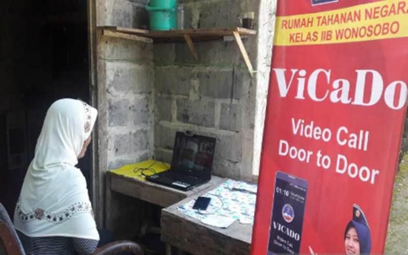 Seorang perempuan melakukan video call dari rumah melalui layar laptop dengan suaminya di dalam rutan dengan memanfaatkan fasilitas Vicado Rutan Wonosobo. - Antara/Heru Suyitno