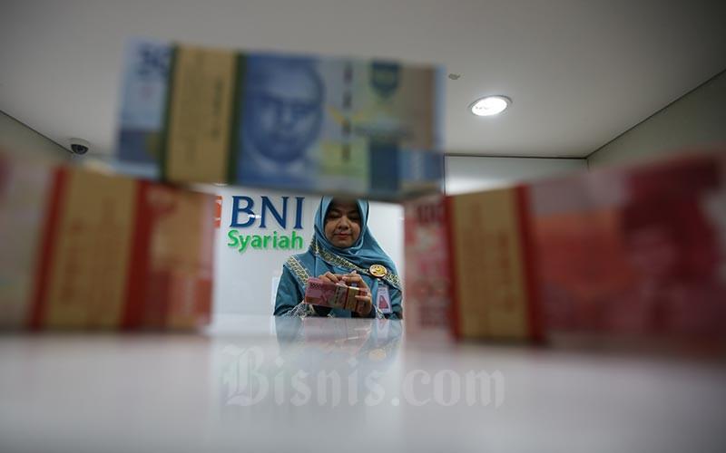 Karyawan menata uang Rupiah di kantor Bank BNI Syariah di Jakarta, Selasa (14/1/2020). Bisnis - Abdullah Azzam