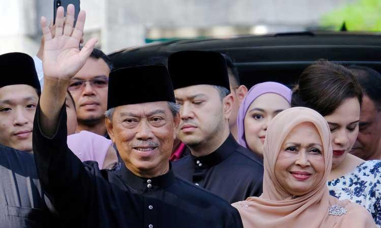 Perdana Menteri Malaysia Muhyiddin Yassin (kiri) melambaikan tangan sebelum berangkat untuk upacara pelantikan di Istana Nasional di Kuala Lumpur, Malaysia, Minggu (1/3/2020). Muhyiddin diangkat sebagai perdana menteri pada 29 Februari oleh raja negara itu untuk mengakhiri pergolakan enam hari perebutan kekuasaan setelah Mahathir Mohamad tiba-tiba mengundurkan diri pada hari Senin karena pertengkaran dalam koalisinya yang dulu. Bloomberg - Samsul Said