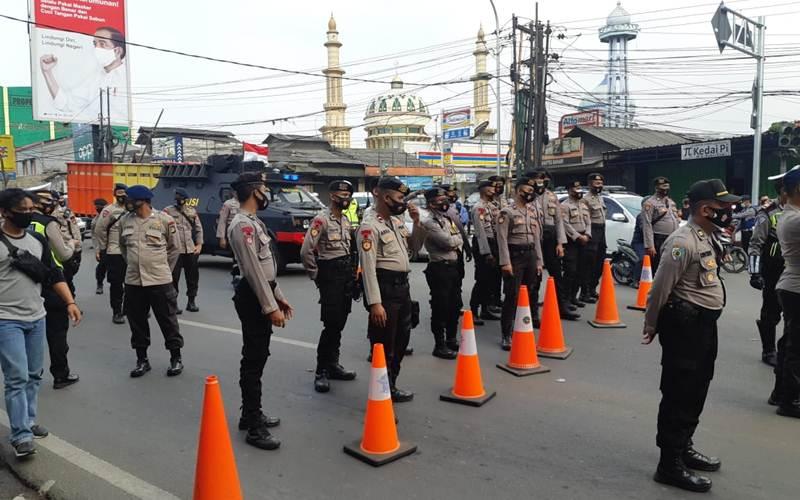 Aparat Kepolisian bersiaga menghadang sekelompok massa bersepeda motor di Jalan Raya Serang, Curug, Tangerang, pada Selasa (6/10/2020). - Bisnis/Aprianus Doni Tolok
