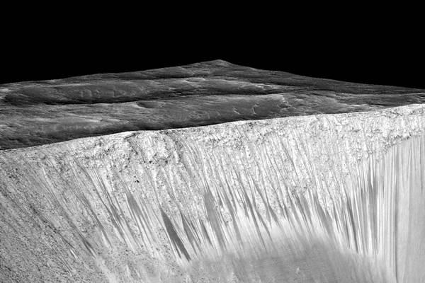 Gambar NASA yang menunjukkan lintasan gelap dan sempit sepanjang 100 meter yang disebut lereng lineae mengalir menuruni bukit di Mars diduga terbentuk oleh aliran air saat ini. - Reuters
