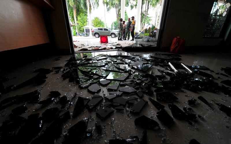 Aparat TNI dan petugas kepolisian berjaga di sekitar pintu utama kantor DPRD Kota Jambi setelah aksi perusakan di Jambi, Rabu (7/10/2020). Saksi mata menyatakan, puluhan orang yang berusia seperti siswa SMA melempari kantor dewan tersebut sekitar pukul 11.00 WIB yang mengakibatkan terjadinya kerusakan pada pintu utama dan beberapa jendela kaca di kantor tersebut. - Antara/Wahdi Septiawan