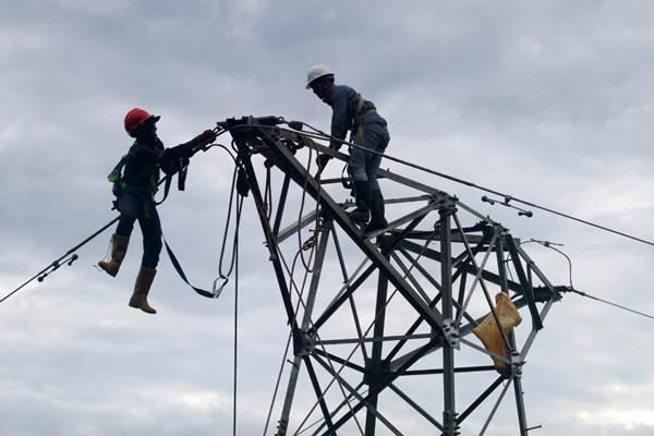 Pekerja memasang jaringan transmisi line 150 kilo volt (KV) Lasusua-Kolaka di Kabupaten Kolaka Utara, Senin (17/12/2018). - Bisnis/Paulus Tandi Bone