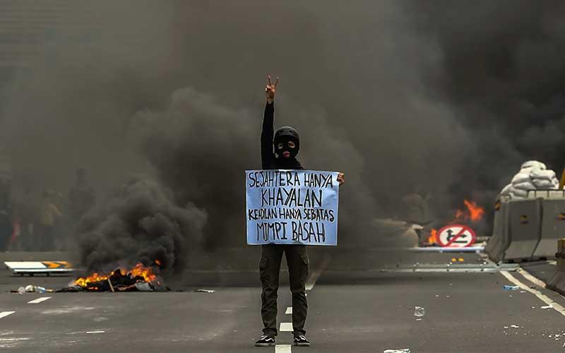 Pengunjuk rasa membawa poster saat bentrokan dengan polisi saat demo menentang UU Cipta Kerja di Jakarta, Kamis (8/10/2020). ANTARA FOTO - Galih Pradipta