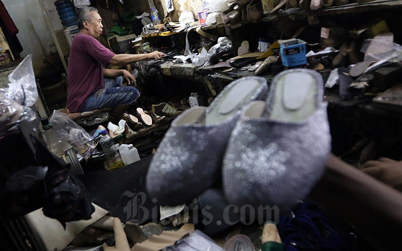 Perajin menyelesaikan pembuatan alas sepatu di Jakarta, Jumat (17/1). Bisnis - Abdullah Azzam