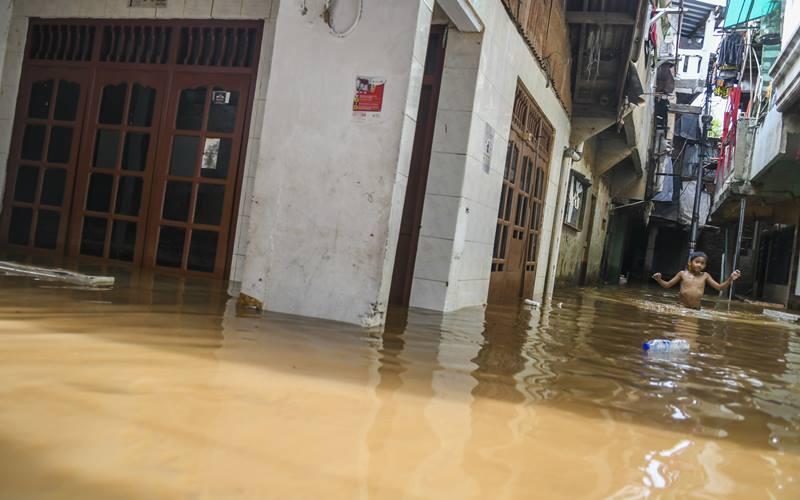 Warga berjalan melintasi banjir di Kebon Pala, Jatinegara, Selasa (22/9/2020). Banjir tersebut terjadi karena luapan Sungai Ciliwung. ANTARA FOTO/Galih Pradipta. - Antara