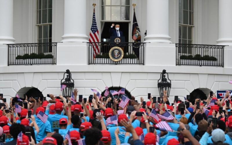 Presiden AS Donald Trump memberi isyarat saat tiba di balkon Gedung Putih di Washington D.C., AS, pada Sabtu (10/10/2020). - Bloomberg