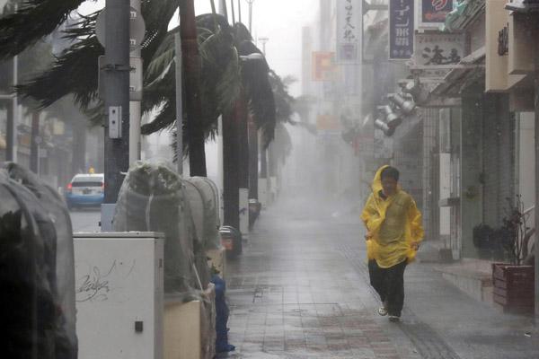Seorang warga berlari di tengah hujan deras akibat Topan Trami di Perfektur Naha di Pulau Okinawa Sabtu (29/9/2018). - Retuers/Kyodo