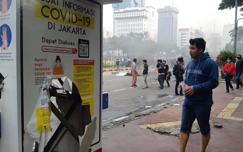 Ilustrasi-Papan informasi tentang Covid-19 dirusak massa yang berdemontrasi menolak omnibus law UU Cipta Kerja di Jalan M.H Thamrin, Jakarta Pusat, Kamis (8/10/2020). - Bisnis/Rayful Mudassir