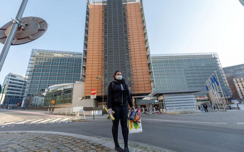 Seseorang mengenakan masker untuk melindungi diri dari penyebaran virus corona, membawa bahan makanan berjalan di luar gedung Berlaymont, yang di dalamnya terdapat kantor Komisi Eropa, di Brussels, Belgia, pada 26 Maret 2020. - Bloomberg/ Olivier Matthys