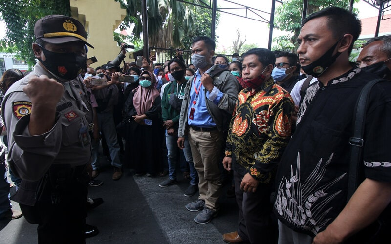 Polisi memberikan penjelasan kepada warga yang antre untuk menjemput keluarganya yang diamankan di Polrestabes Surabaya, Jawa Timur, Jumat (9/10/2020). Polrestabes Surabaya mengembalikan 231 anak kepada keluarganya dari 253 orang yang ditangkap saat unjuk rasa buruh Tolak UU Cipta Kerja pada Kamis (8/10) kemarin, sedangkan 22 orang sisanya ditetapkan menjadi tersangka atas kasus dugaan perusakan fasilitas umum. - Antara/Didik Suhartono