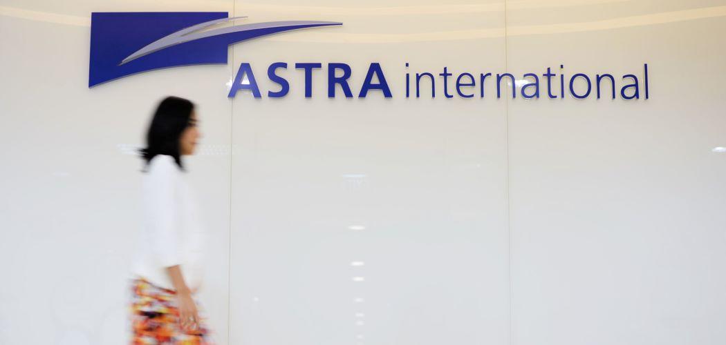 Karyawan melintas di depan logo PT Astra International Tbk. - Bloomberg / Dimas Ardian